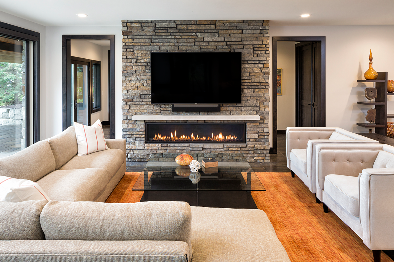 Living room with fireplace with stone surround. Tv sits above the fireplace. Modern home decor and furniture.