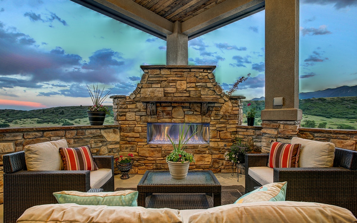 Outdoor room with beautiful outdoor fireplace with stone surround. Chairs and couch sit in front of the fireplace.