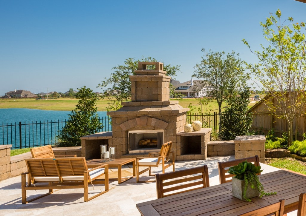 Outdoor patio with fireplace and dining area overlooking a lake.