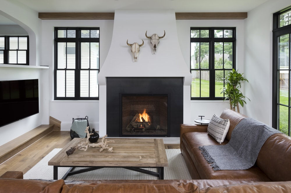 Modern living room with a large fireplace and hard wood floors. Room is accented with western home decor.