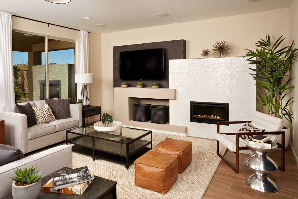 Living room with fireplace with tile surround and modern furniture and decor.